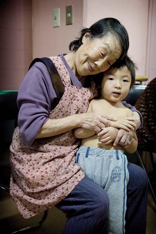 Tokyo – 3rd of December 2009 – Kotohen nursery and nursing home in the Edogawa district. Tsukaguchi Tsuroko , 80, enjoying the visit of the kids.