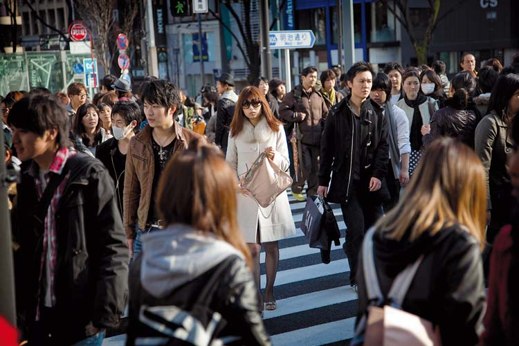 Tokyo, Omotesando, February 28, 2010 – Sunday afternoon, a young japanese woman walking in the crowd on the Omotesando crossing.